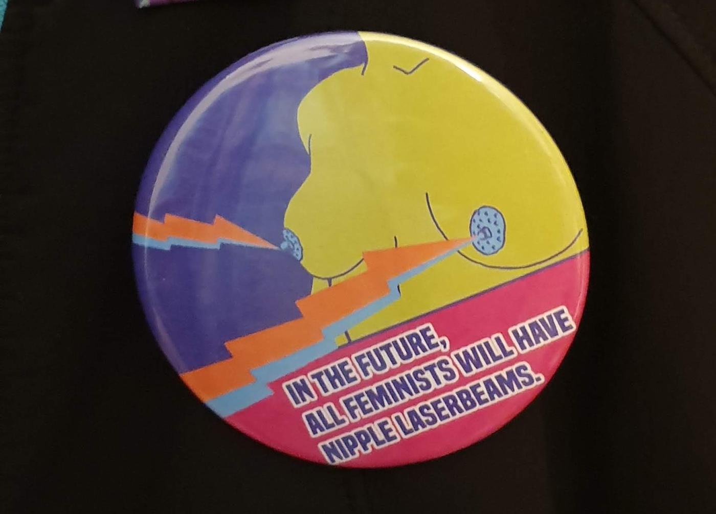 "a black coat with a round badge on. The badge image is of a naked human torso with green skin and blue nipples. There are lightning bolts shooting from the breasts. The badge text reads ""in the future, all feminists will have nipple laserbeams"""