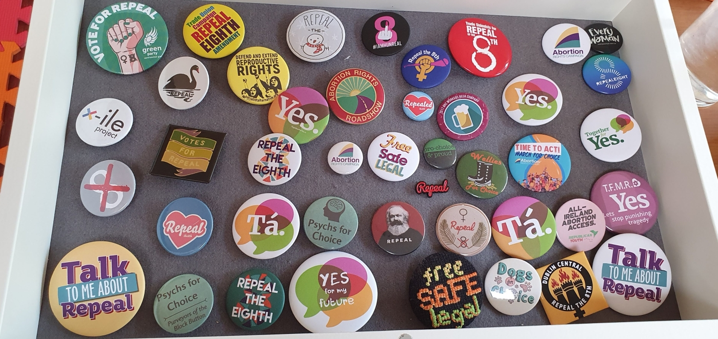 A shadow box with a large number of badges displayed. They all relate to the campaign to repeal the 8th and to abortion rights